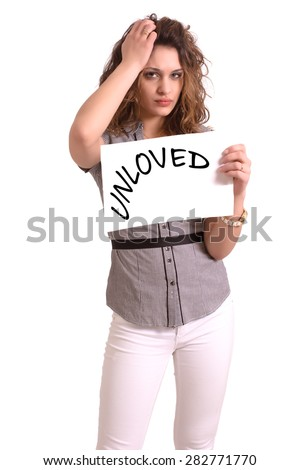 Young attractive woman holding paper with Unloved text on white background