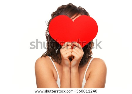 Young attractive woman holding red paper heart like a valentine card and hiding her face. Shot over white background