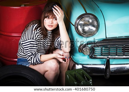young attractive woman in a baseball cap sits tired in the garage near the retro car with tools. Girl holding pliers and took hold of the head. - stock photo