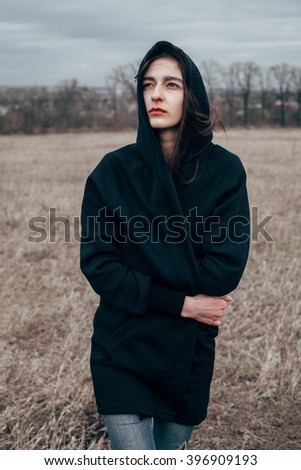 Young attractive woman in a black cape in the field. looking up