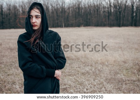 Young attractive woman in a black cape stands in a field in windy weather