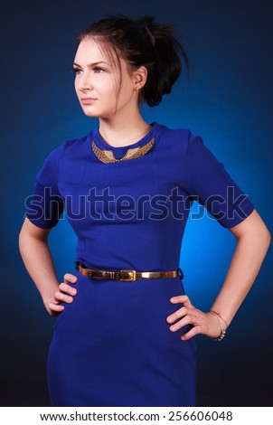 Young attractive woman in a blue evening dress over blue background - stock photo