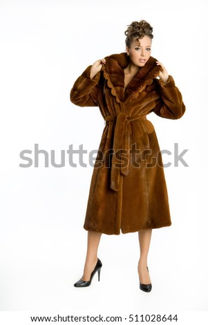 Young attractive woman in a fur coat on an isolated studio background
