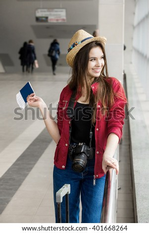 young attractive woman in a red coat and hat standing in the terminal or at the station with a suitcase and passport and tickets. The girl met on a trip. - stock photo