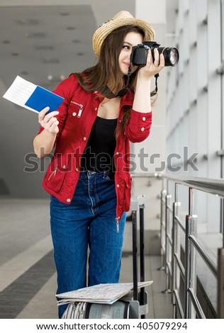 young attractive woman in a red coat and hat standing in the terminal or at the station with a suitcase and photographs. The girl met on a trip. - stock photo