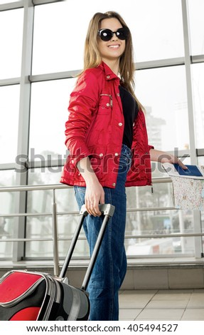 young attractive woman in a red coat and hat standing in the terminal or at the station with a suitcase and passport and tickets. The girl met on a trip.
