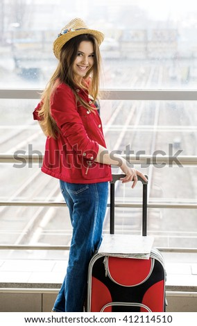 young attractive woman in a red coat and hat standing in the terminal or at the station with a suitcase. The girl met on a trip.She looks into the camera - stock photo