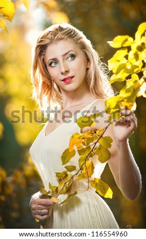 Young attractive woman in a romantic autumn scenery. Blonde woman posing in white dress in autumn scenery.Girl with  leaves in hand and fall yellow maple garden background - stock photo