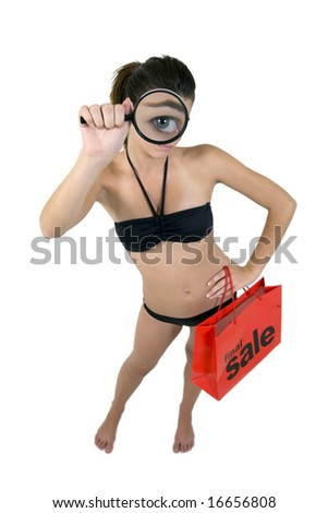 Young attractive woman in a sexy bikini magnifying her big blue eye holding a final sale shopping bag - stock photo