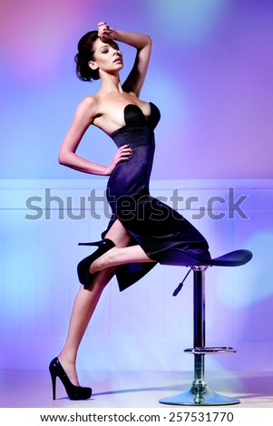 Young attractive woman in black elegant dress acting - stock photo