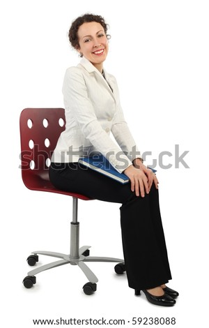 young attractive woman in business dress sitting on chair and holding a book, side view, isolated on white - stock photo