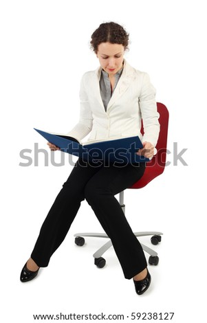 young attractive woman in business dress sitting on chair and reading a book, front view, isolated on white
