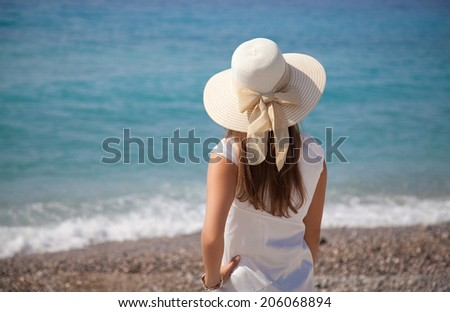 Young attractive woman in hat and white dress near the sea on a summer day. Enjoying looking view of beach sea on hot summer day. Travel holidays vacation  - stock photo