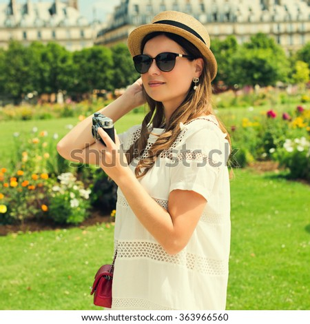 young attractive woman in hat, white dress, red bag and retro camera poses against Paris. Fashion and city style.  - stock photo