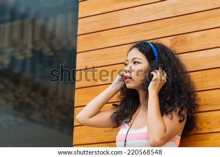 Young attractive woman in headphones listening to the music - stock photo