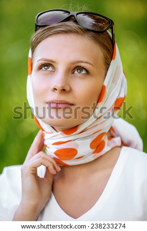 Young attractive woman in headscarf with sunshades, on green background of summer city park. - stock photo
