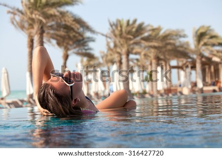 Young attractive woman in in pool with head thrown back side view. Girl at travel spa resort pool. Summer luxury vacation. - stock photo