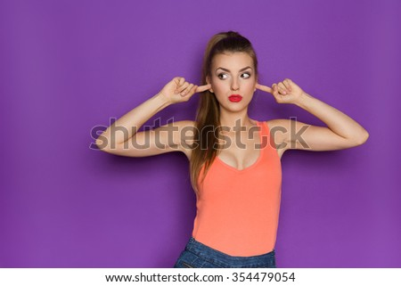 Young attractive woman in jeans shorts and orange shirt showing with thumb up. Three quarter length studio shot on teal background. - stock photo