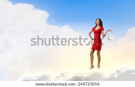 Young attractive woman in red dress with bag in hand - stock photo