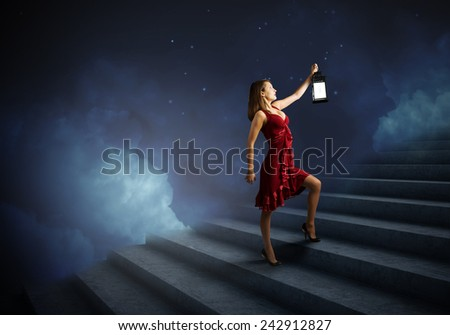 Young attractive woman in red dress with lantern walking in darkness