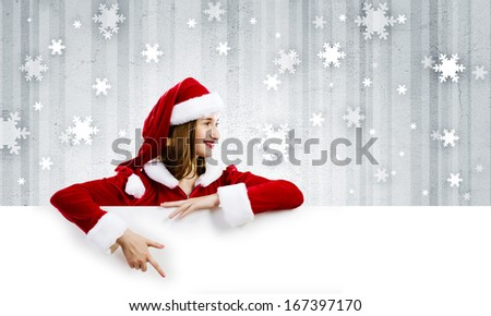 Young attractive woman in santa suit holding blank banner. Place for text - stock photo