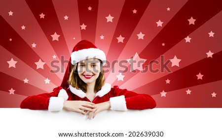 Young attractive woman in santa suit holding blank banner. Place for text