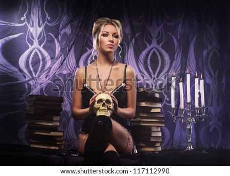 Young attractive woman in sexy lingerie posing in gothic interior - stock photo
