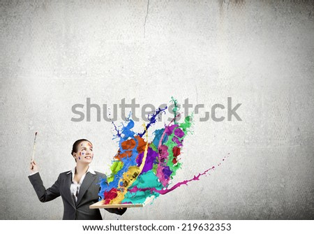 Young attractive woman in suit with paint brush in hand
