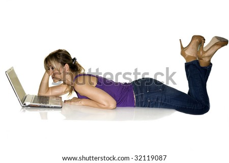 Young attractive woman in tshirt blue jeans on professional laptop computer, on white backdrop