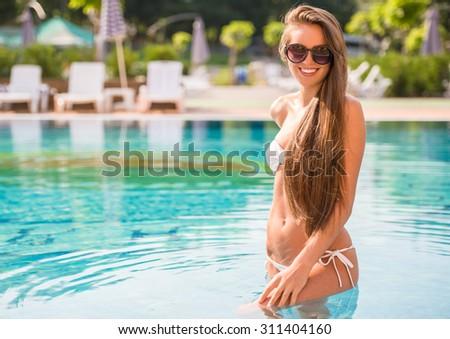 Young attractive woman in white bikini is posing in water in swimming pool. - stock photo