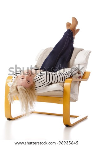 Young, attractive woman is laying upside down in an armchair. She is smiling happily. - stock photo