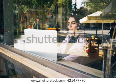 Young attractive woman is making plans for the future, sitting in front of an open laptop computer in a cozy coffee shop.Modern young business woman thinking about a new project,looking at the window. - stock photo