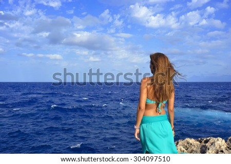 young attractive woman looking at ocean horizon thoughtful standing on rock cliff by sea shore in glamour dress under summer blue sky in relax and vacation concept - stock photo