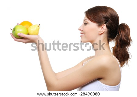 young attractive woman looking ay the fruits in her hands