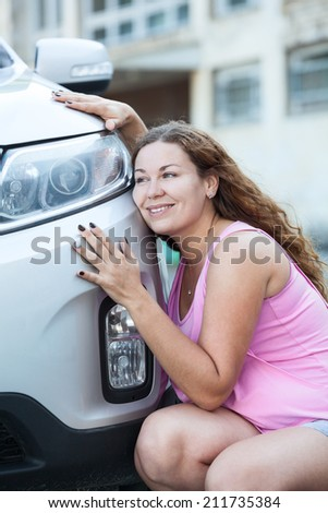 Young attractive woman loving her new car