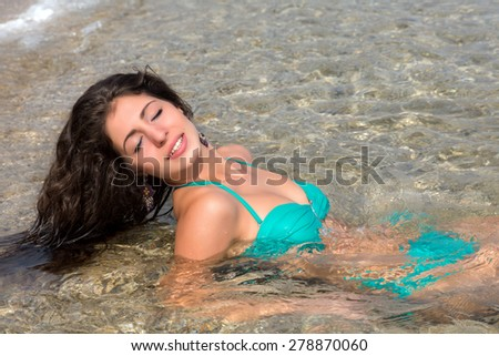 Young attractive woman lying on the beach enjoying the waves - stock photo