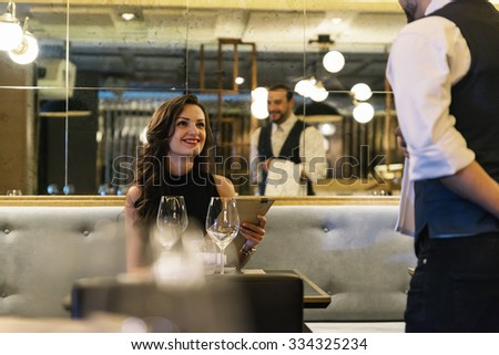 Young attractive woman making order at elegant restaurant - stock photo