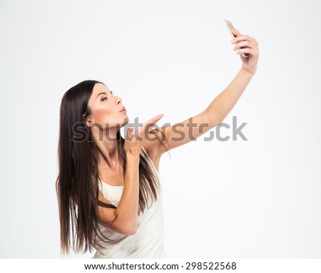 Young attractive woman making selfie photo on smartphone isolated on a white background - stock photo