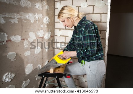 young attractive woman of the side, concenctrated and cutting a long wood with a yellow saw indoors