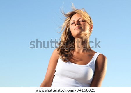 young attractive woman on sky background - stock photo