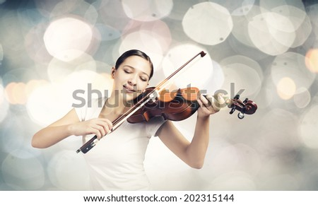 Young attractive woman playing violin with bokeh lights at background - stock photo