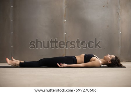young attractive woman practicing yoga lying stock photo