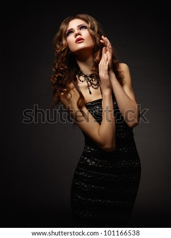 Young attractive woman praying over dark background - stock photo