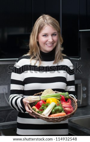 Young, attractive woman presents a basket with vegetables in the kitchen - stock photo