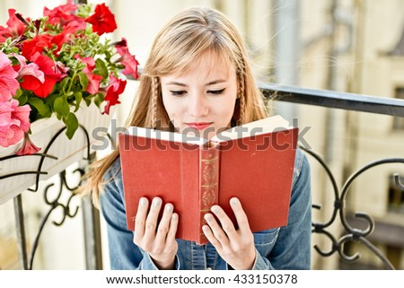 Young attractive woman reading a book outdoor sitting on the balcony