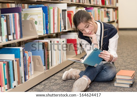 Young attractive woman reading a book while sitting on the floor in front of a bookshelf