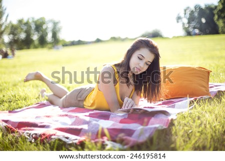 Young attractive woman reading a magazine on a meadow in a park - stock photo