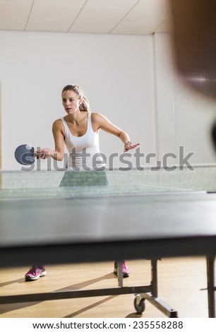 Young attractive woman returning a shot during an indoor game of table tennis - stock photo