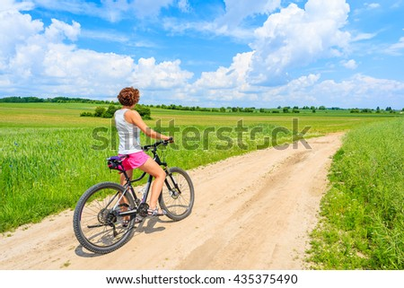 Young attractive woman riding a bike on rural road in green summer landscape, Poland
