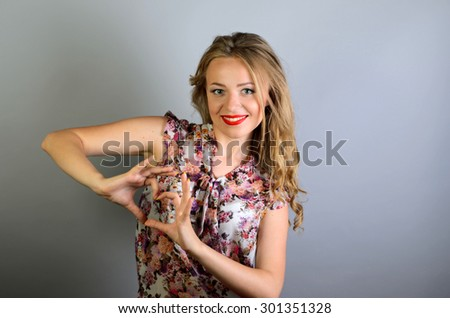 young attractive woman showing heart shape with her fingers - stock photo